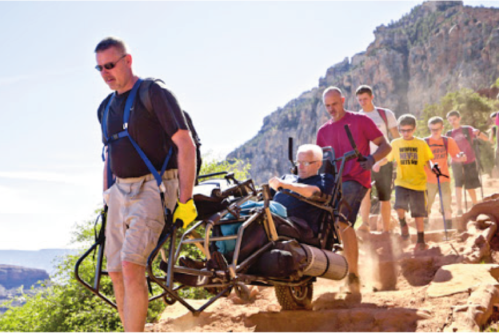 Group of hikers walking with a TrailRider on a cliff side.