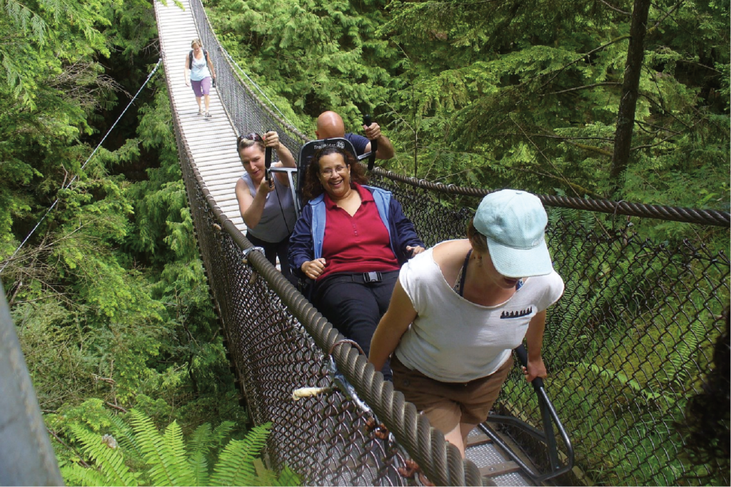 Hikers walking across the Capilano Suspension Bridge with a TrailRider.